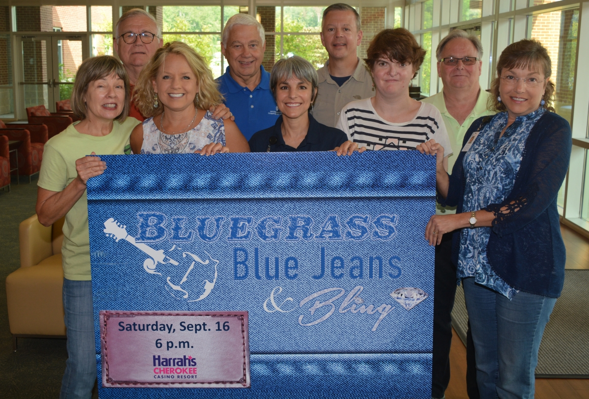 "Group of people hold up sign that says ""Bluegrass, Blue Jeans & Bling"" with the date of Sept. 16, 2017"
