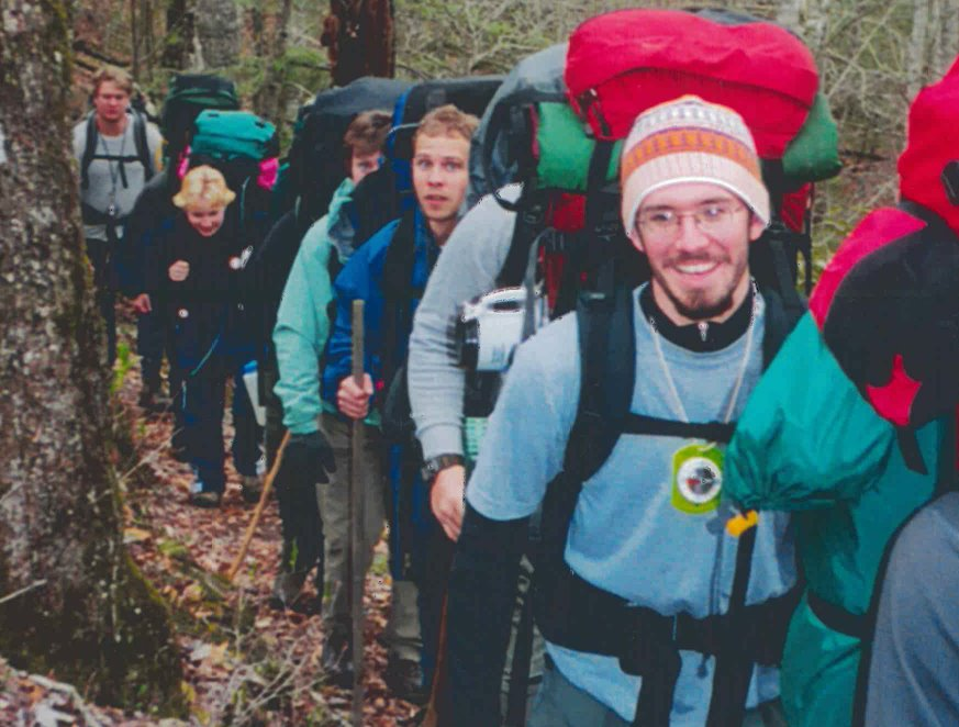 A man smiles and carries a heavy backpack while hiking a trail next to classmates