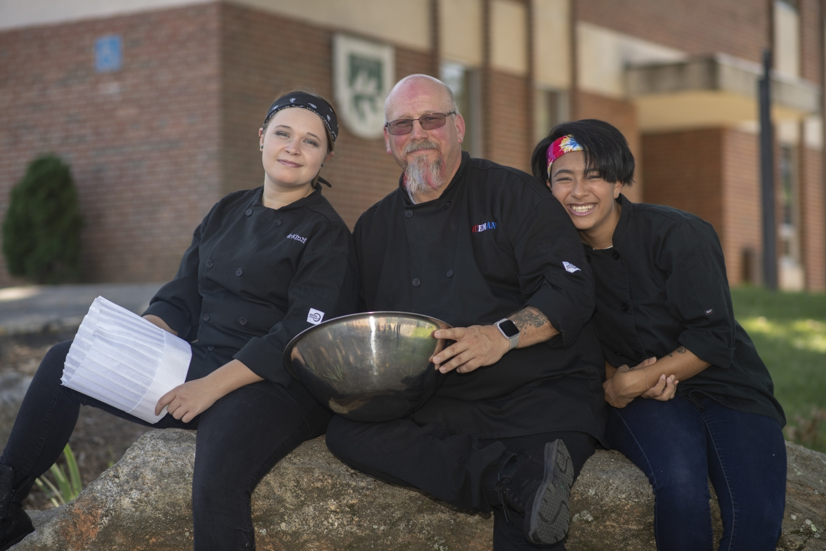 Three culinary students smile in black uniforms while huddled closely outside