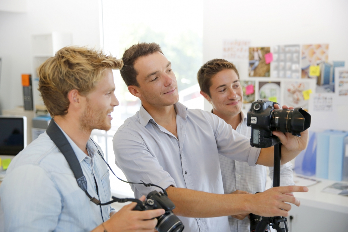 A male photographer instructor examines a photograph on the camera alongside two male students