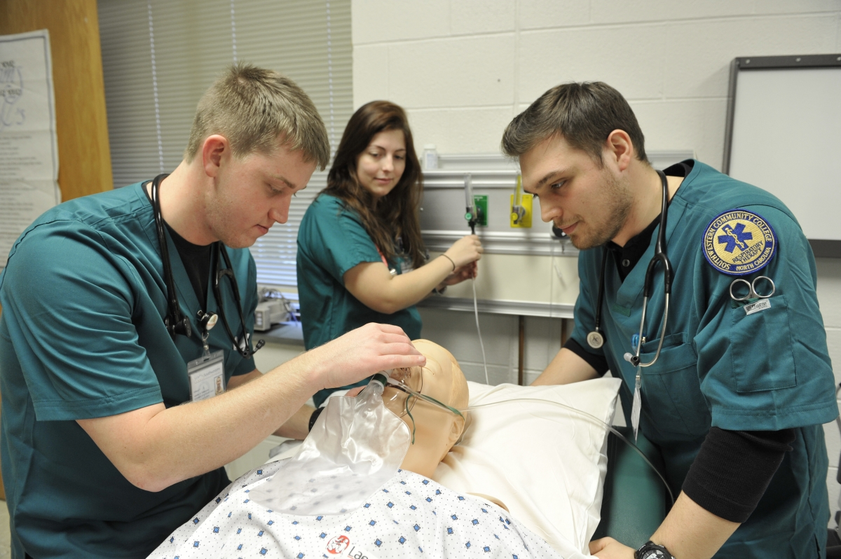 Photo of three students working with respiratory equipment