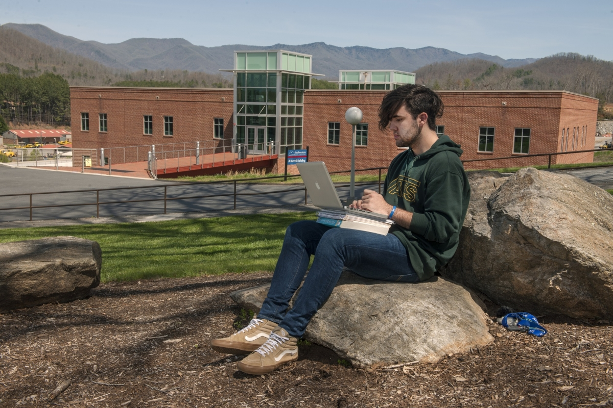 A young man uses a laptop while sitting on a rock outside a school building