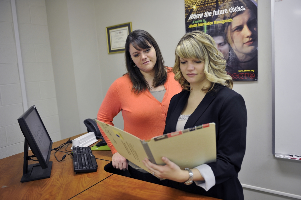 Photo of two students looking at files