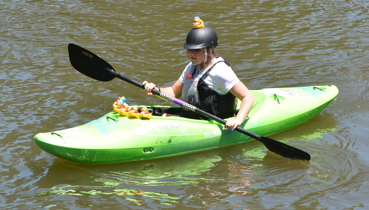 A volunteer picks up loose ducks in the Tuckaseigee River last May in Bryson City.