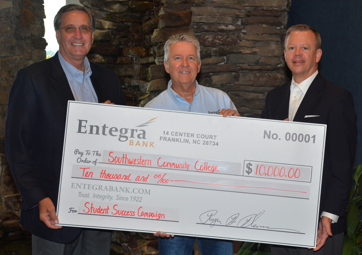 Three men pose with a large check in front of a stacked rock decor
