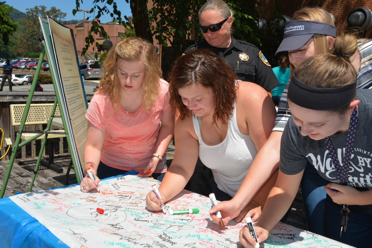 Four female students sign their names to a proclamation as a school resource officer looks on outdoors at our Jackson Campus.