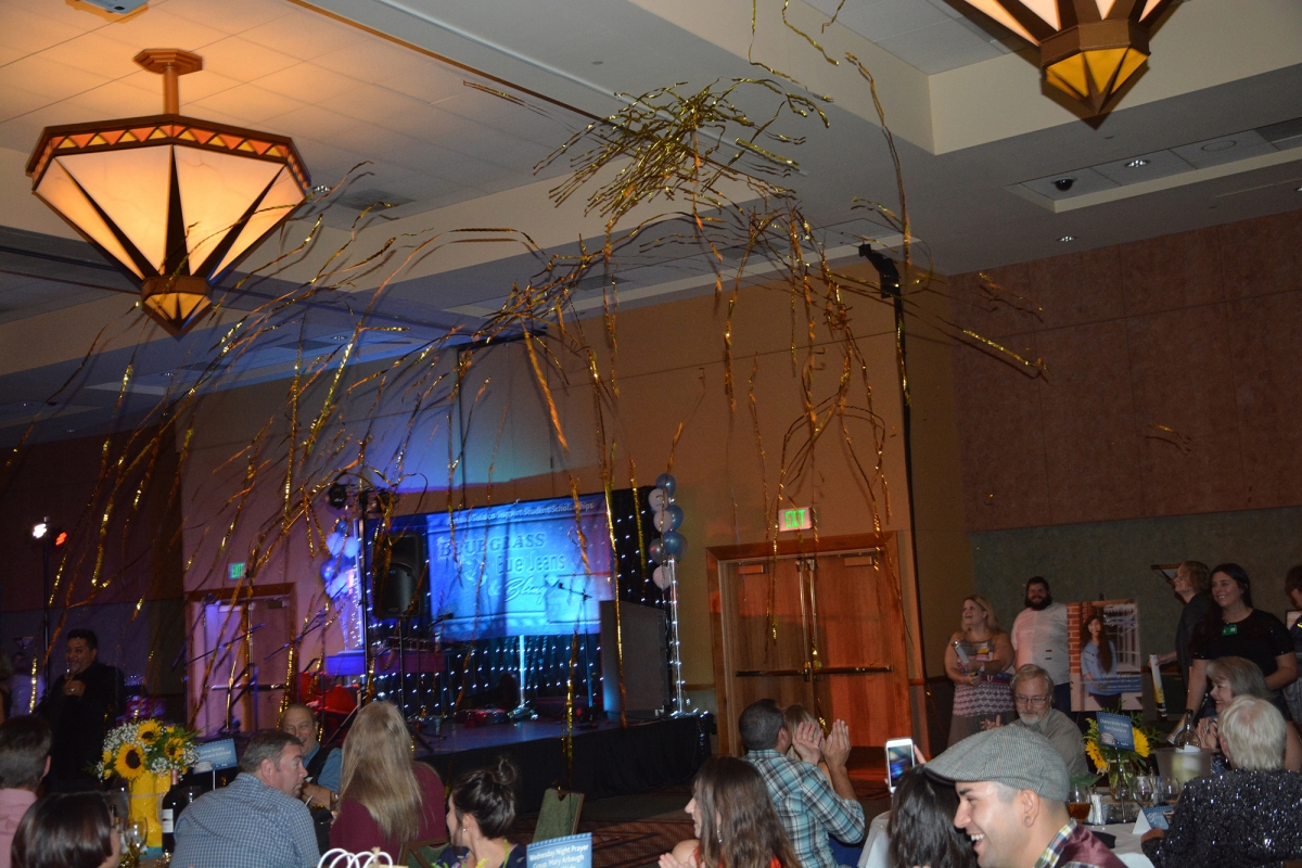Gold Streamers fly through the air in a ballroom.