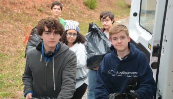 Five students load large bags filled with donations into a van.
