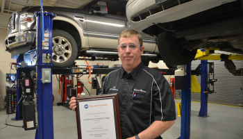 Man holds plaque in garage with cars on lifts in background.