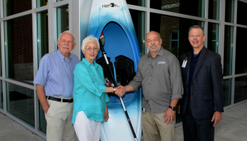 Three men and a woman stand beside a kayak outside a building on SCC's Jackson Campus in Sylva.