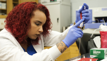 Female student conducts a test in SCC's lab.