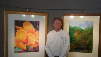 Randy Lanier standing between two paintings one is a flower the other a tree scene