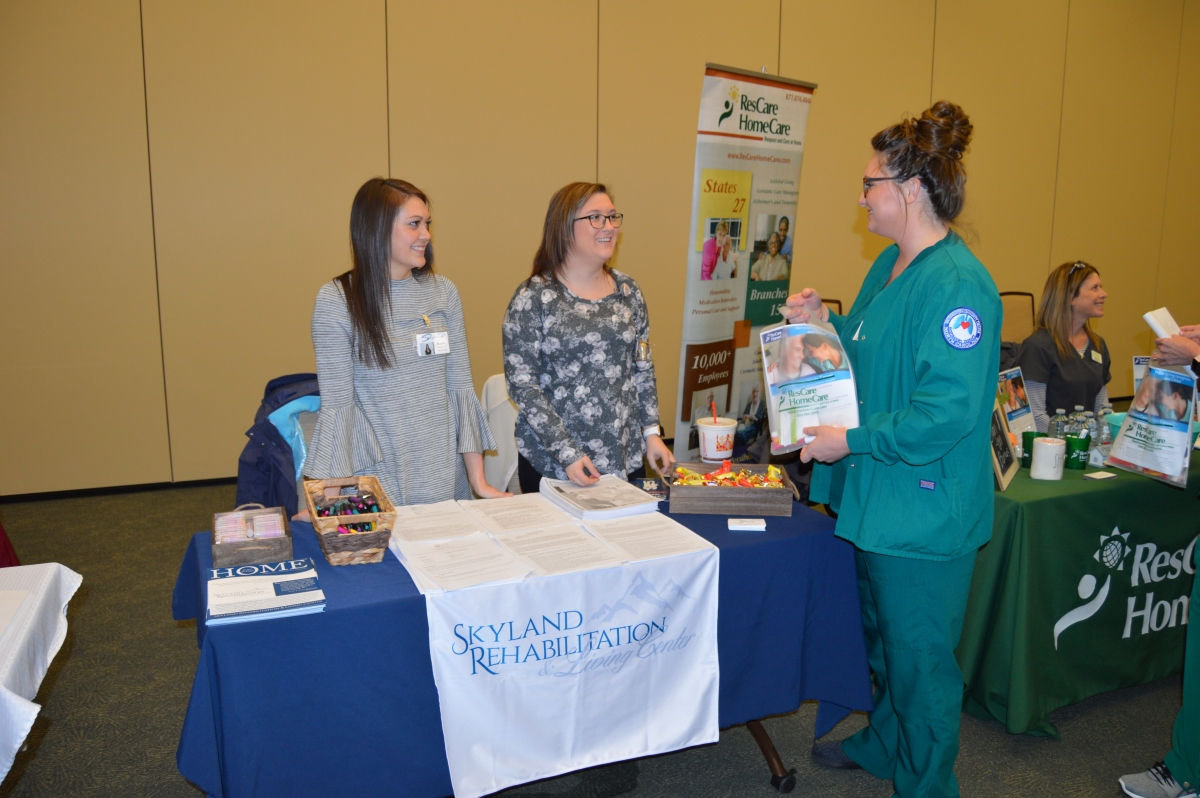 A young woman in nursing scrubs interviews with two other women at a job fair