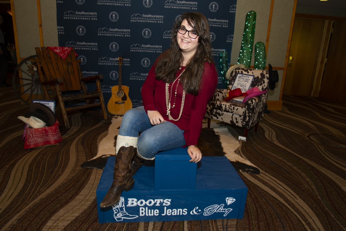 Young woman smiles while posing in a pair of cowboy boots