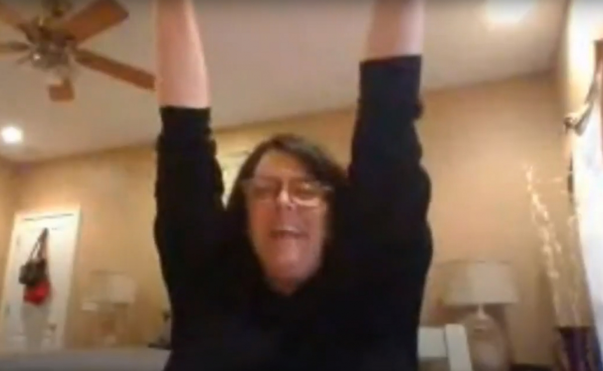 Woman raises her arms in celebration in a grainy online photo