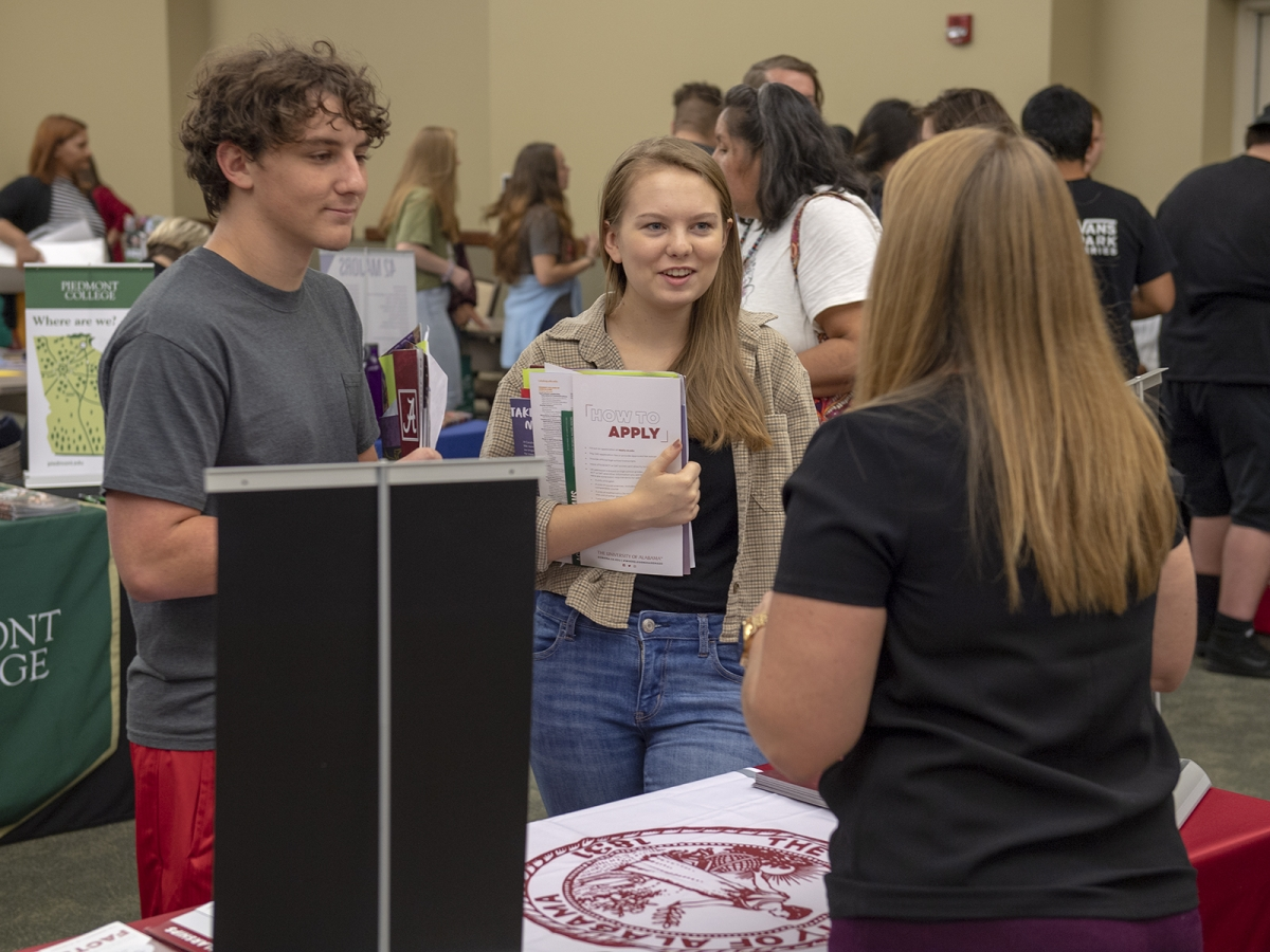 Young man and woman standing in front of a college fair booth.