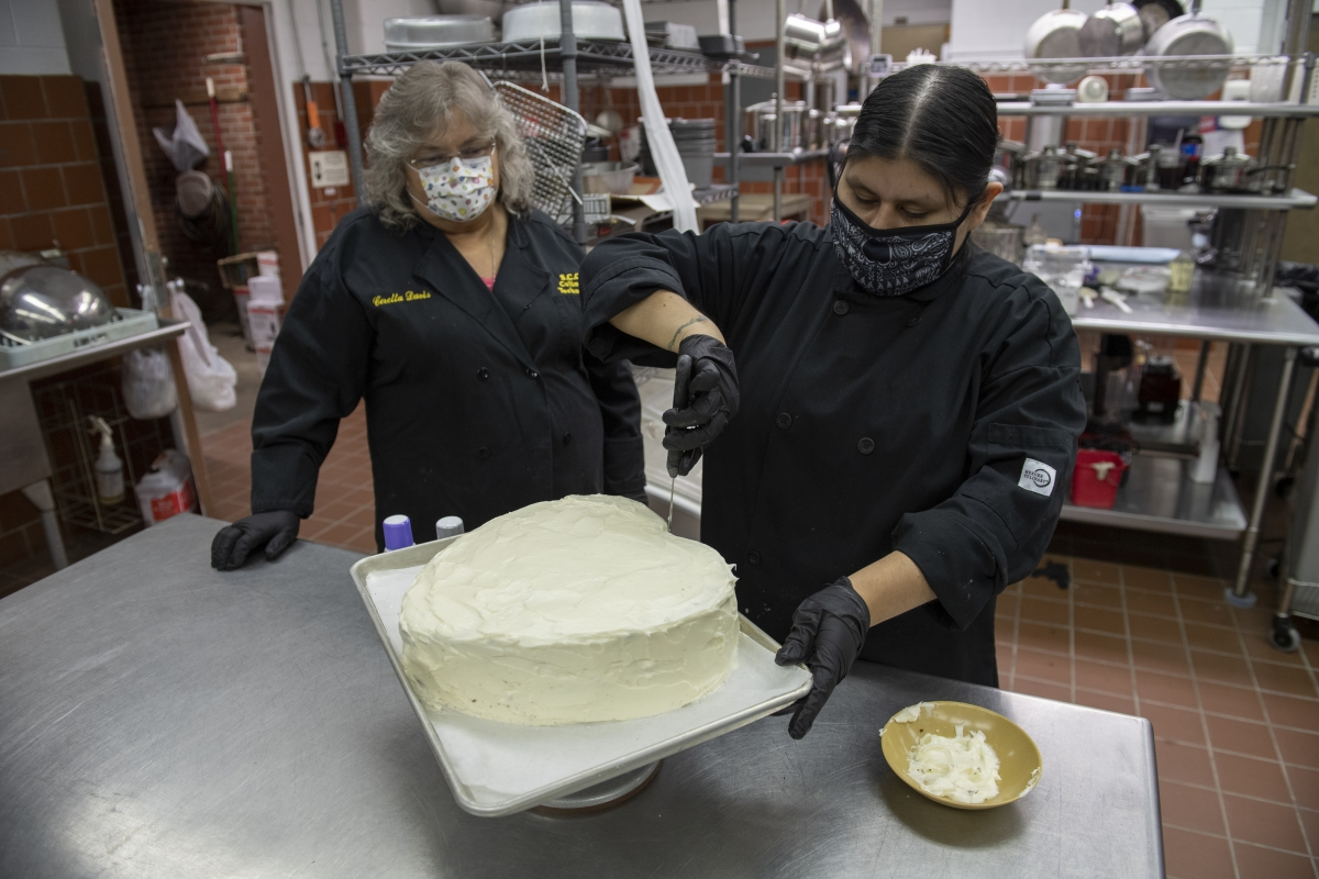 A female chef instructor watches a female student making a cake