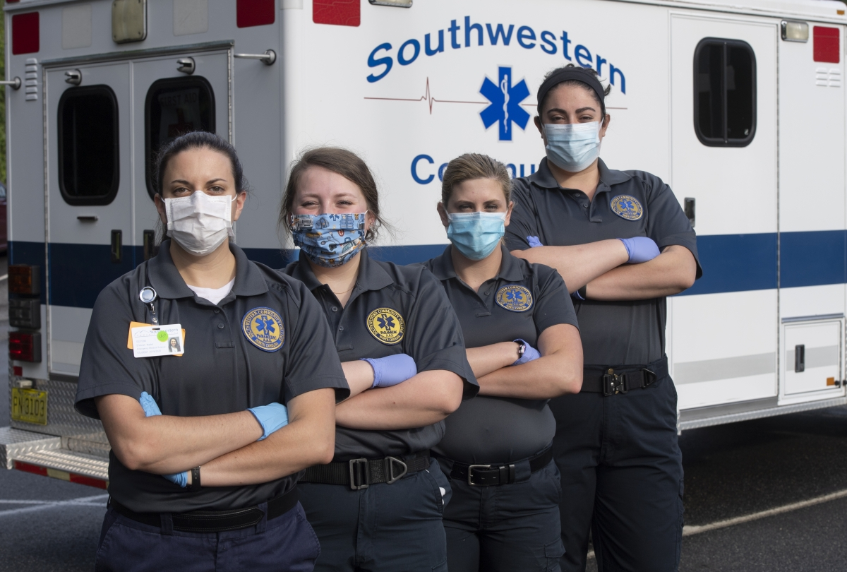 A group of female EMS students stand in a line wearing masks while crossing their arms
