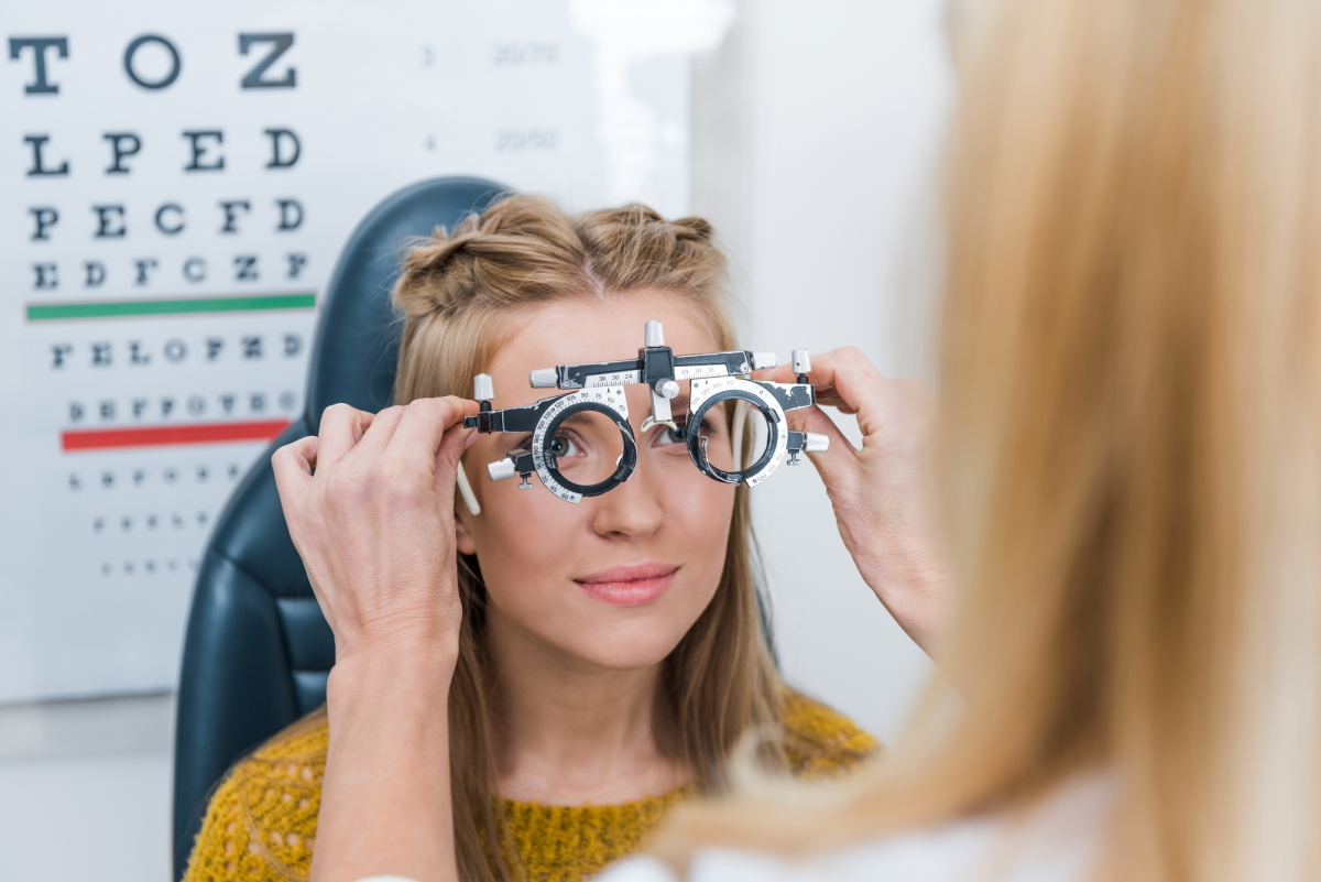 A young woman is getting eye glass measurements
