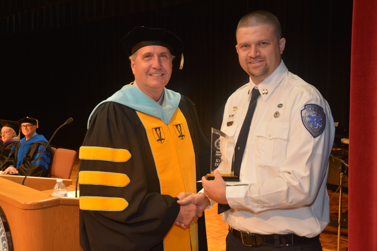 A male college president in a cap and gown presents an award to a male graduate from the emergency medical science program