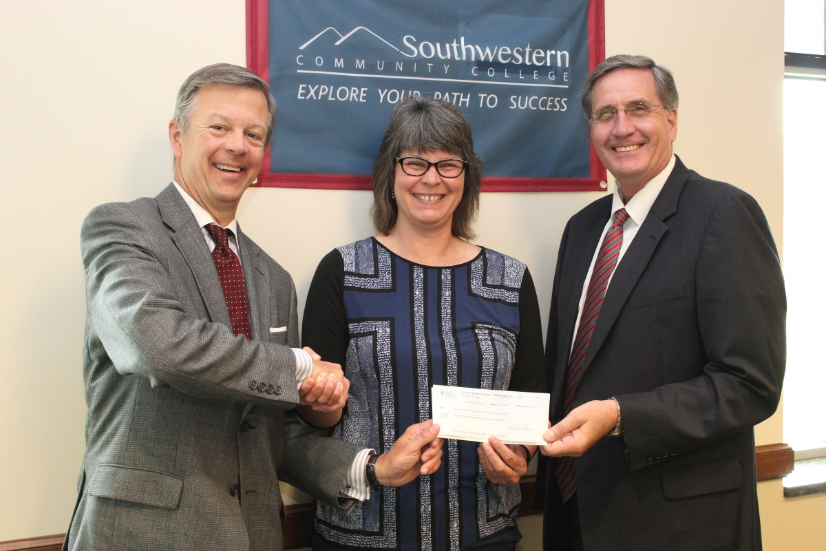 A woman smiles while shaking hands with two men and presenting a check