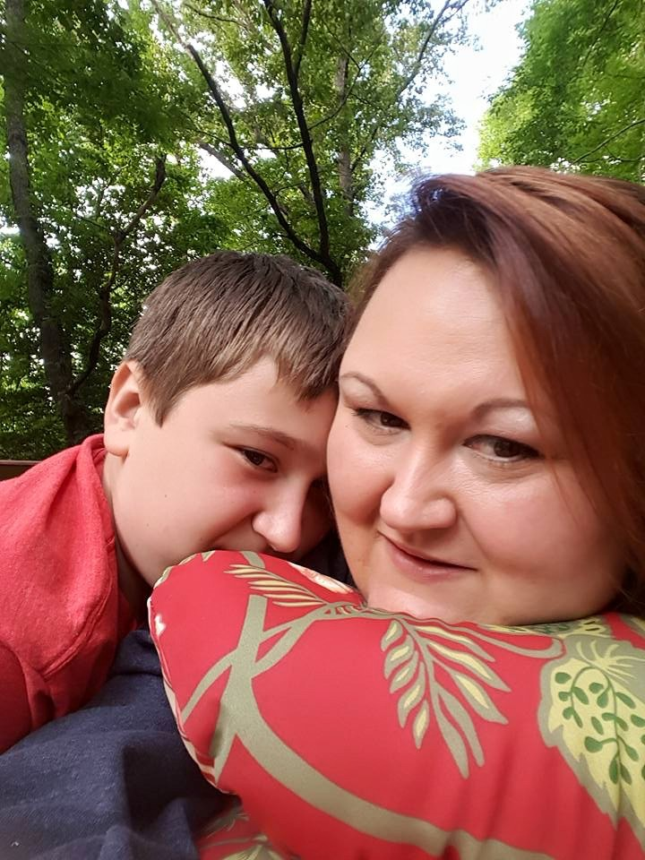 Woman and her son posed for a selfie outdoors underneath a tree.