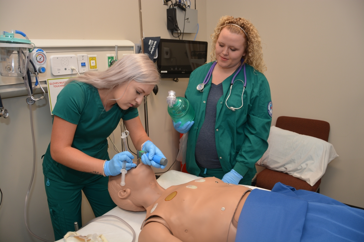 Two young women provide respiratory therapy to a health mannequin.