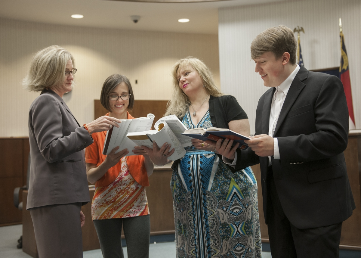 Female attorney stands with her students and reads legal books in a local court room.