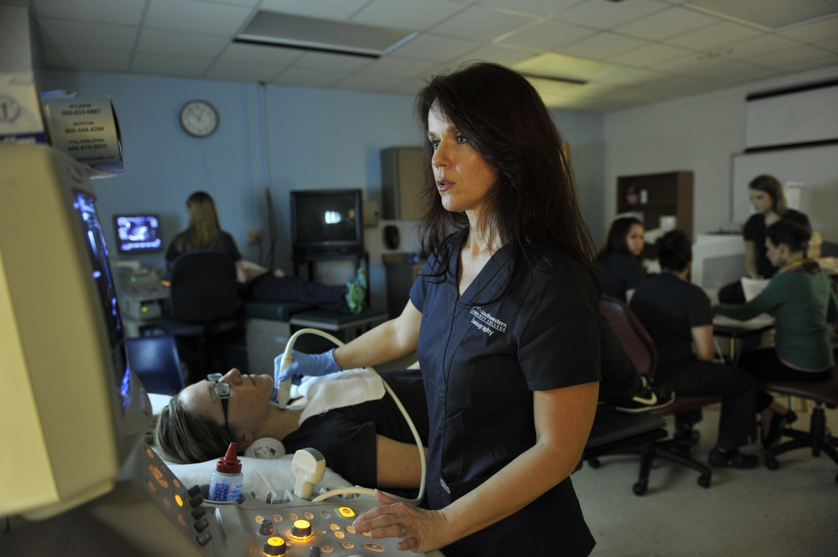 Photo of female student training with ultrasound equipment in classroom