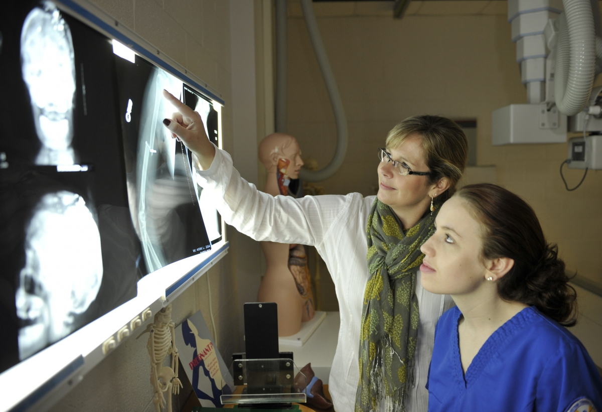 Photo of Meg Petty with student looking at Xrays