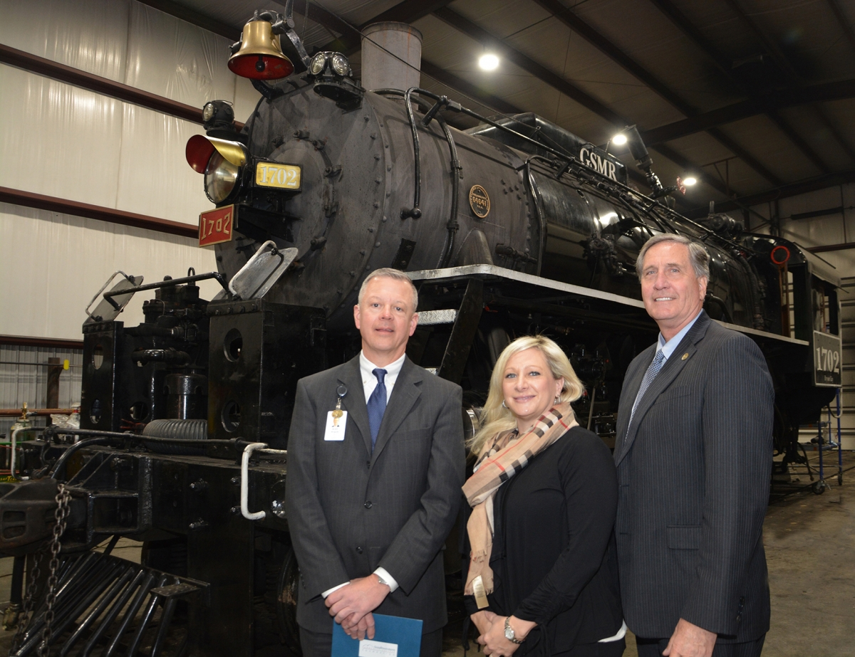 Two men and a lady stand in front of a recently renovated steam locomotive.
