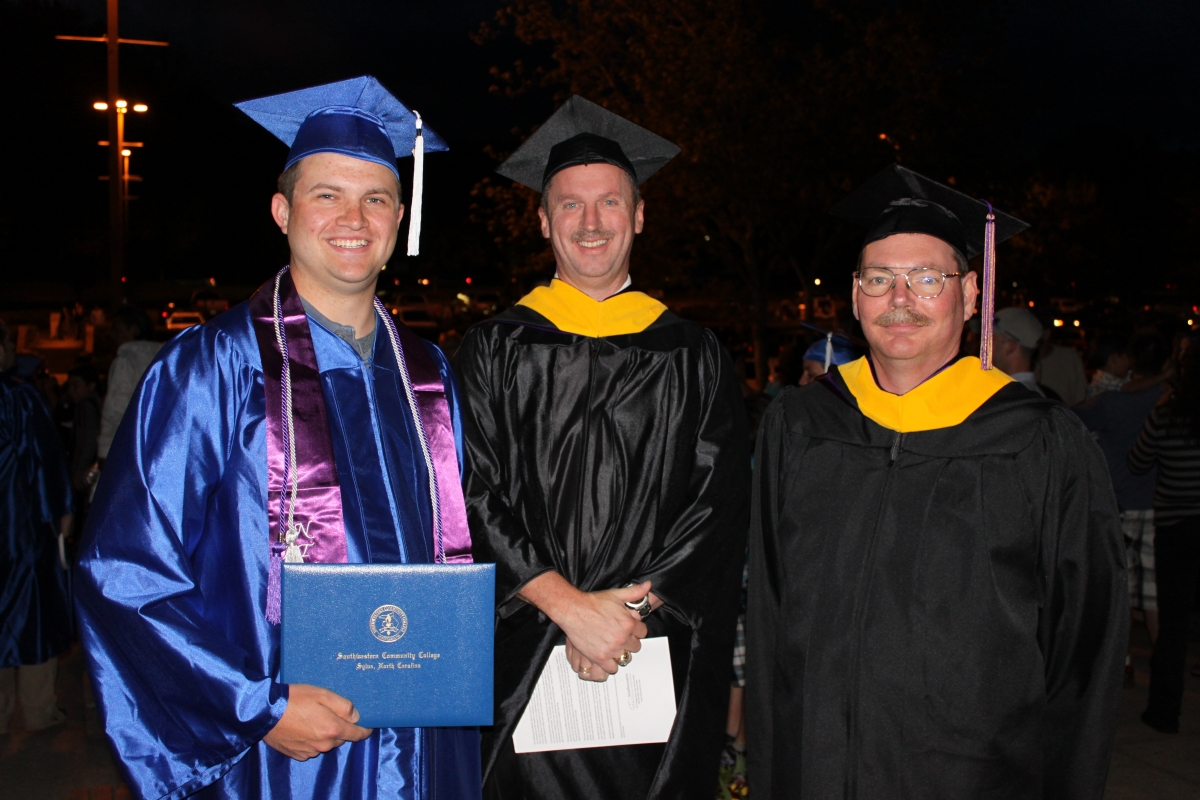 Graduate and two faculty members pose outside at night