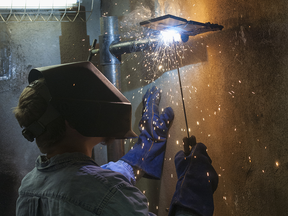 A student welds, producing an arc