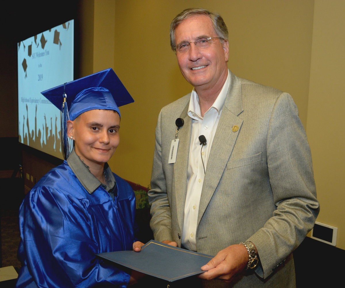 Student wearing graduation cap and gown accepts diploma from college president