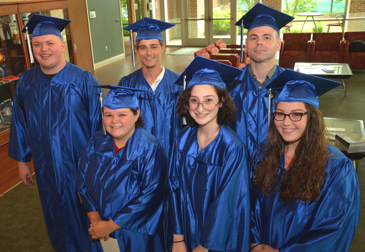Six students pose wearing their graduation caps and gowns