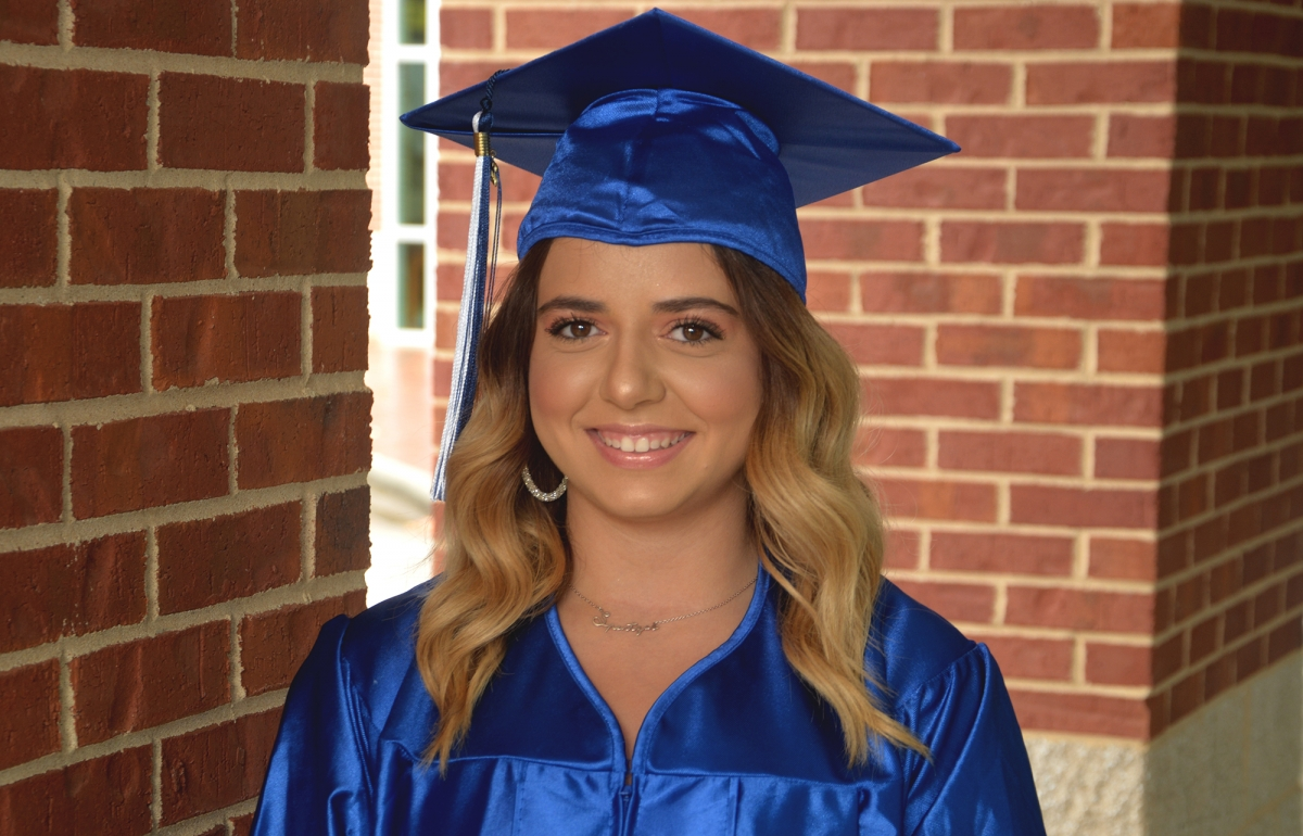 Woman wearing blue graduation cap and gown stands in front of brick columns