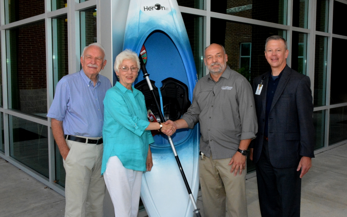 Three men and a woman stand beside a kayak outside a building on SCC's Jackson Campus.