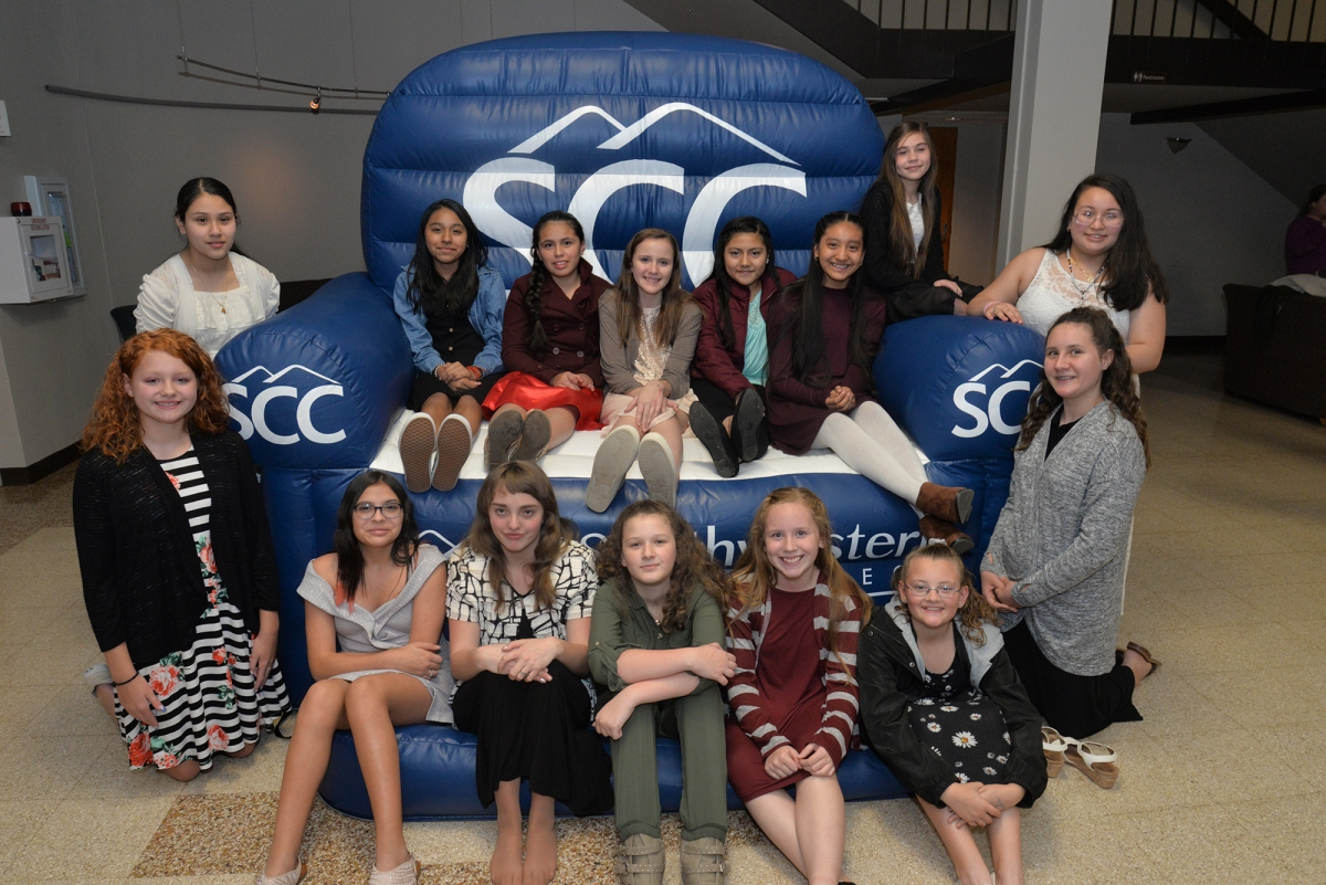 More than a dozen students pose on a blue inflatable chair with SCC logos.