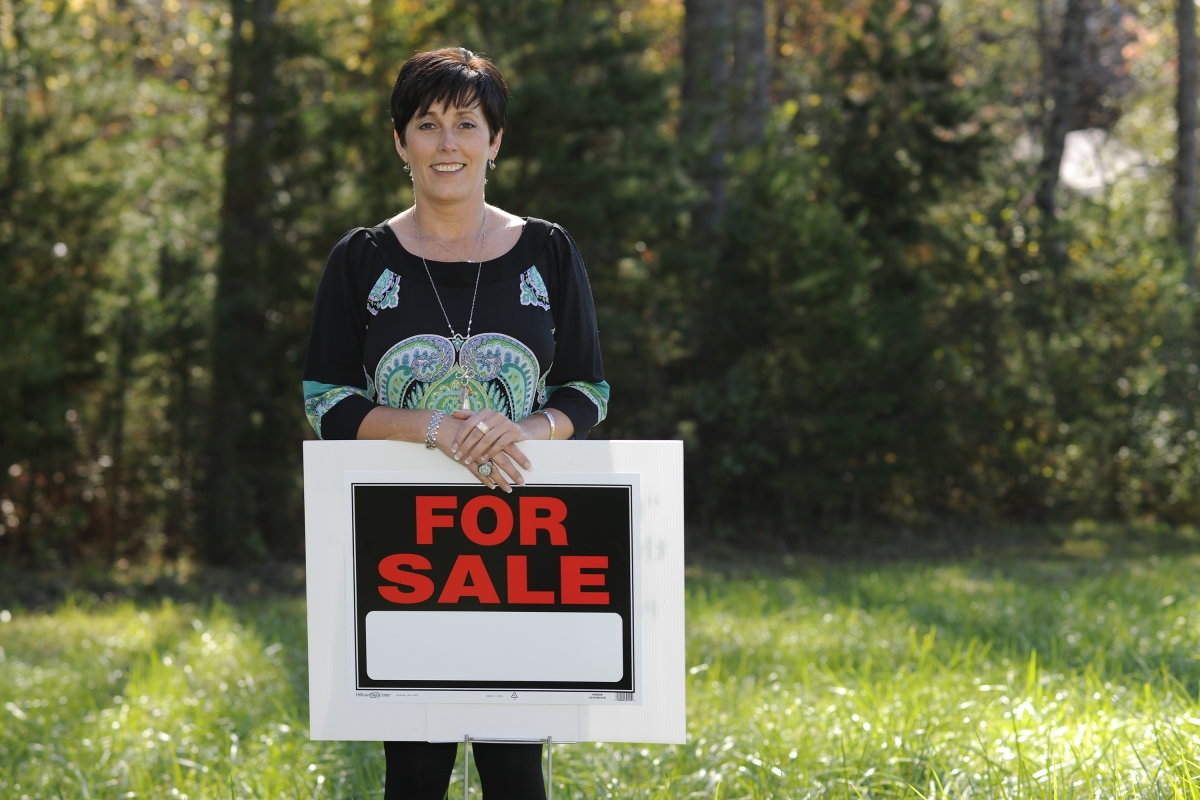 "Woman is pictured outdoors with a ""For Sale"" sign"