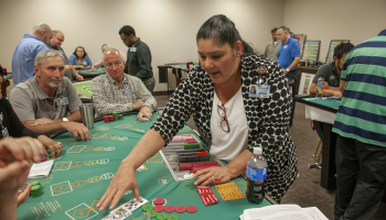 Woman deals a hand of blackjack to several classmates inside a casino training room.