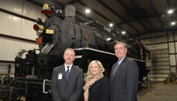 Two men and a woman stand in front of a recently renovated steam locomotive.