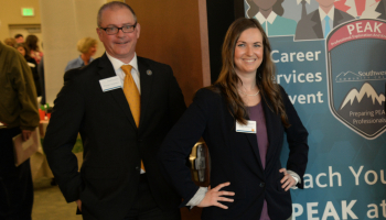Man and woman stand at welcome table during a recent Job Fair.