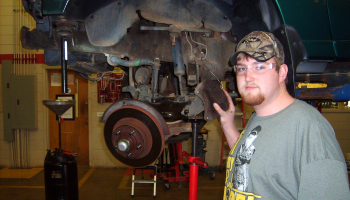 Male student wearing goggles stands beside an automobile that is on a large mechanized jack.