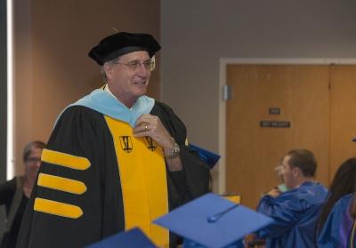 College president, wearing academic regalia, addresses graduates inside Balsam Center