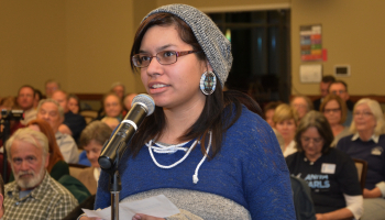 Young lady speaks into a microphone