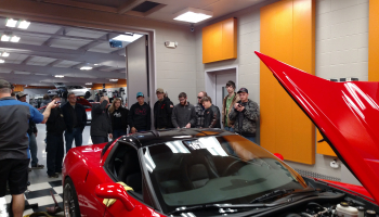 Students surround a red sports car at Passion Performance