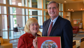 Veterans Council chair Lyn Lazar and SCC president Dr. Don Tomas holding the framed military seals.