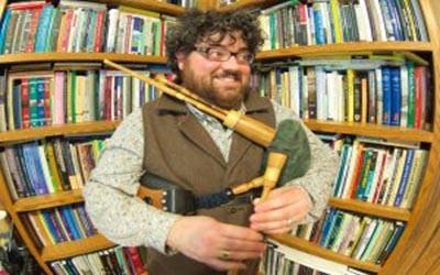 Tiber Falzett holding bagpipes
