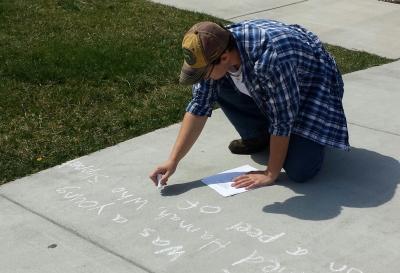 Male student writes a poem in sidewalk chalk on SCC's Jackson Campus.