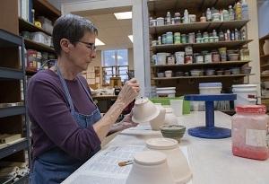 A woman paints a handmade bowl